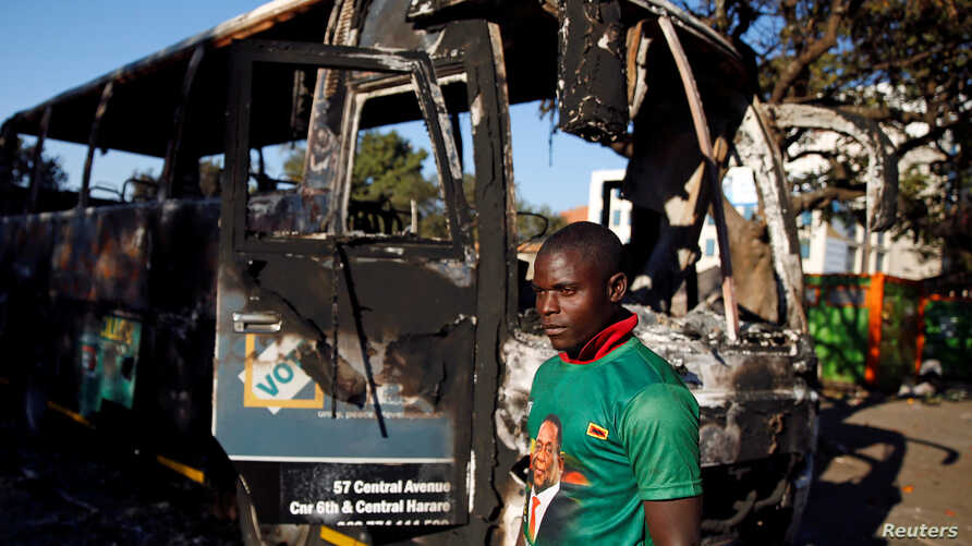 A supporter of the ruling ZANU-PF walks past a burnt vehicle at the party's offices a day after the clashes between security forces and opposition protesters in Harare, August 2, 2018.