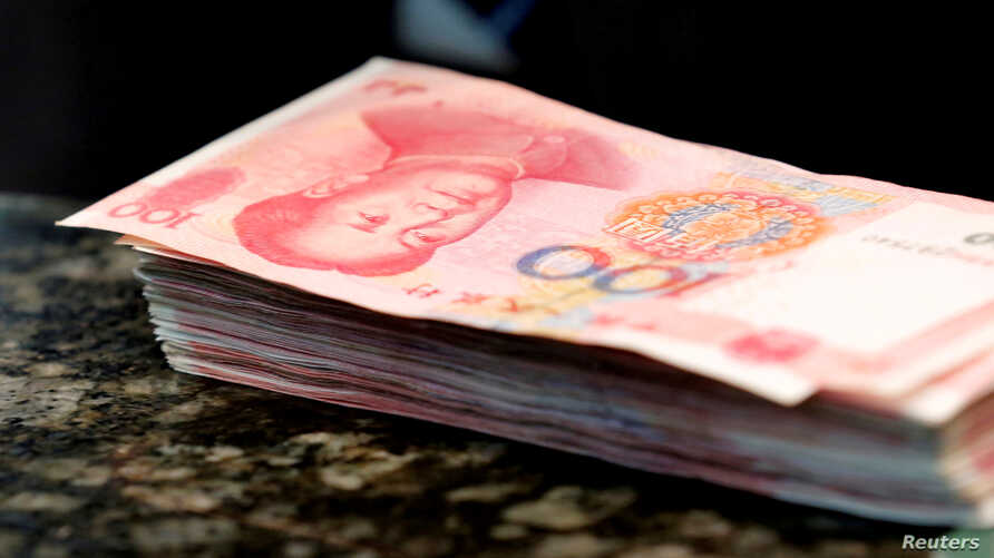 FILE - Chinese 100 yuan banknotes are seen on a counter of a branch of a commercial bank in Beijing, China, March 30, 2016.