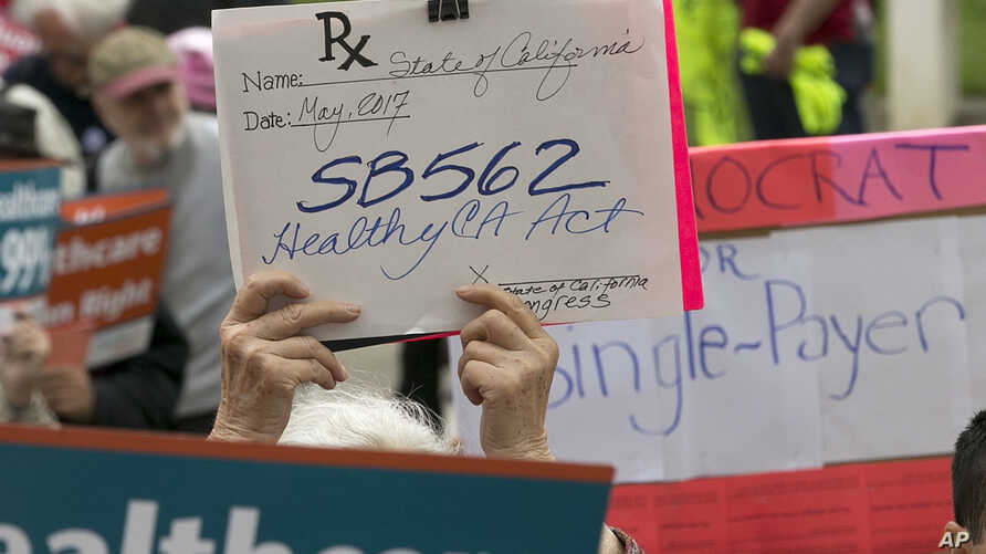 Caroline Elam holds up a mock prescription order calling for passage of SB562, a single-payer health care bill, during a march to the Capitol in Sacramento, Calif., April 26, 2017.