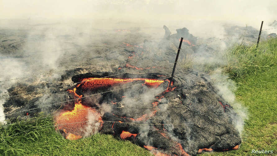 The lava flow from the Kilauea Volcano is seen advancing across a pasture between the Pahoa cemetery and Apa'a Street, in this U.S. Geological Survey (USGS) image taken near the village of Pahoa, Hawaii, Oct. 25, 2014.