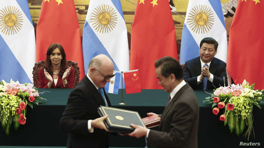 Argentinian President Cristina Fernandez de Kirchner and Chinese President Xi Jinping applaud as Argentinian Foreign Minister Hector Timerman, left, and Chinese Foreign Minister Wang Yi exchange documents during a signing ceremony at the Great Hall o