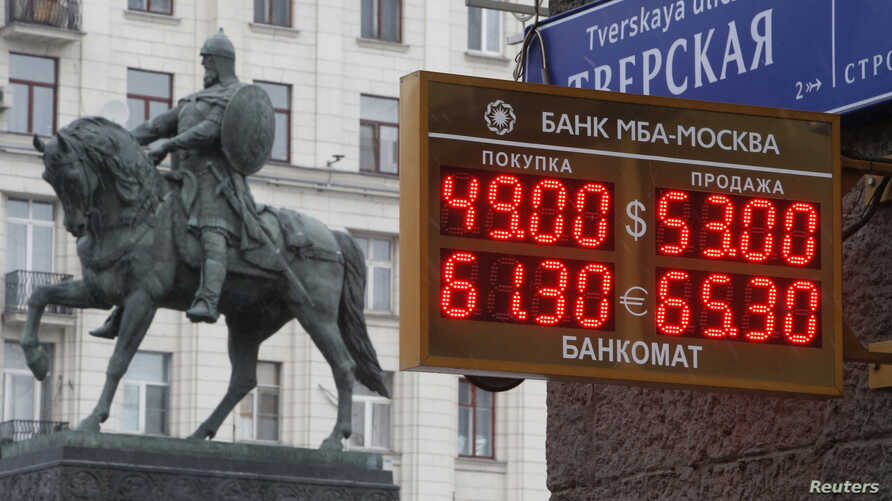 A board showing currency exchange rates, in front of a monument to Prince Yury Dolgoruky who founded Moscow in 1147, in the capital Moscow, Dec. 1, 2014.