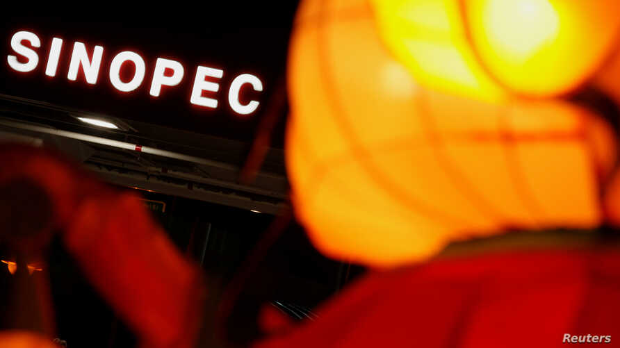 FILE - A Sinopec sign displayed at its gas station is seen behind a Chinese New Year lantern installation in Hong Kong, Feb. 5, 2013.