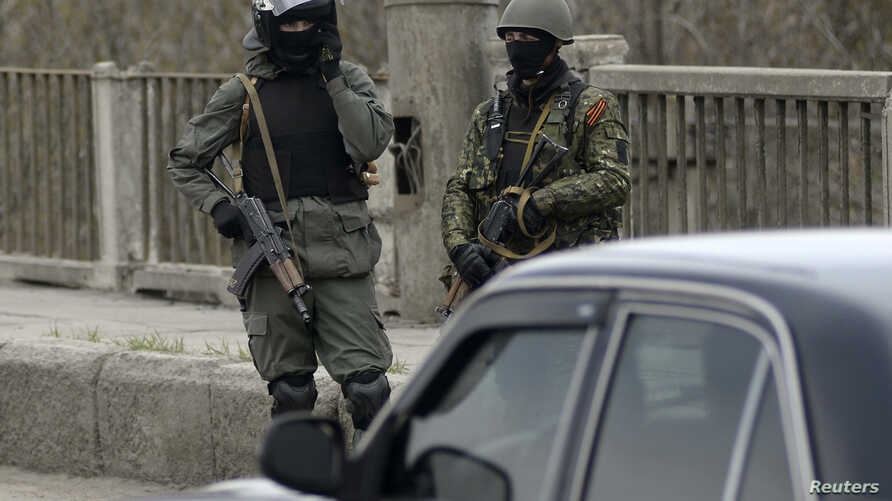 Pro-Russia armed men stand at an improvised checkpoint in Slovyansk, eastern Ukraine, April 12, 2014.