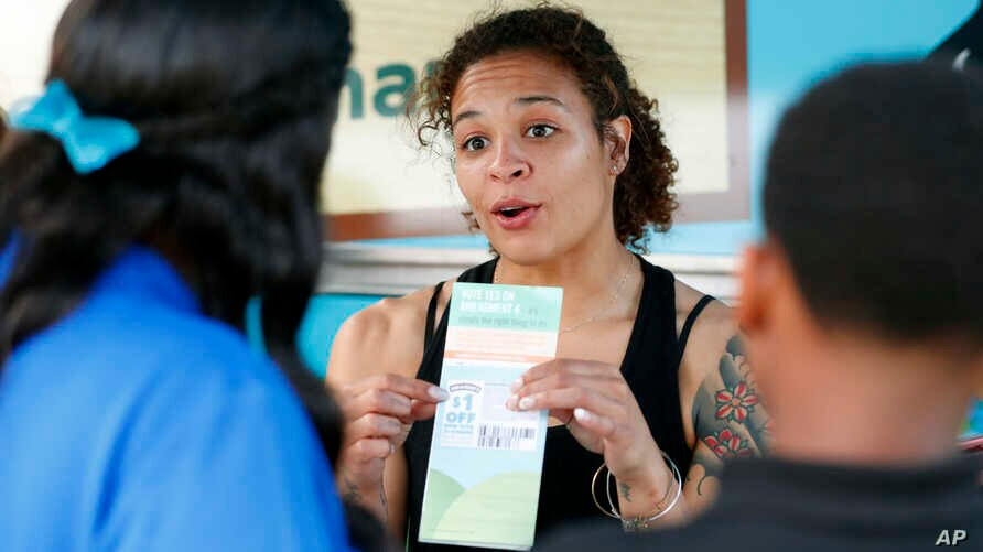 FILE - Jessica Jones, center, speaks to people about Amendment 4 at Charles Hadley Park in Miami, Oct. 22, 2018. Amendment 4 asked voters to restore the voting rights of people with past felony convictions, and Floridians approved it on Nov. 6, 2018.