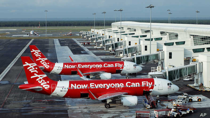 FILE - In this Nov. 10, 2014 photo, AirAsia Airbus A320-200 passenger jets are parked on the tarmac at low cost terminal KLIA2 in Sepang, Malaysia.