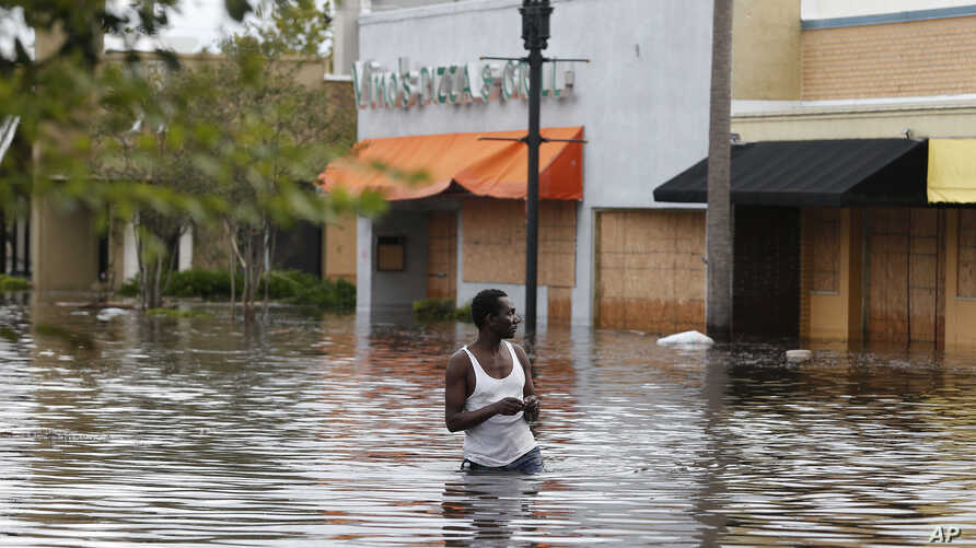 John Duke wades through a flooded street to try to salvage his flooded car in the wake Hurricane Irma, Sept. 11, 2017, in Jacksonville, Fla.