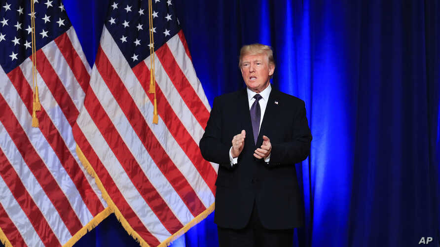 President Donald Trump applauds after delivering a speech, laying out a national security strategy, in Washington, Dec. 18, 2017.