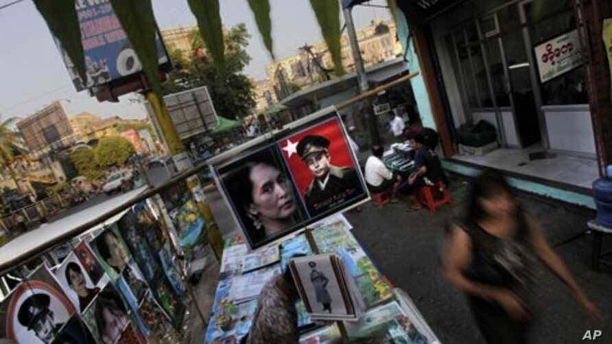 In this photo taken on Feb 23, 2012, people walk past a roadside stall selling the posters of Burmese democracy icon Aung San Suu Kyi and her late father in Rangoon, Burma.