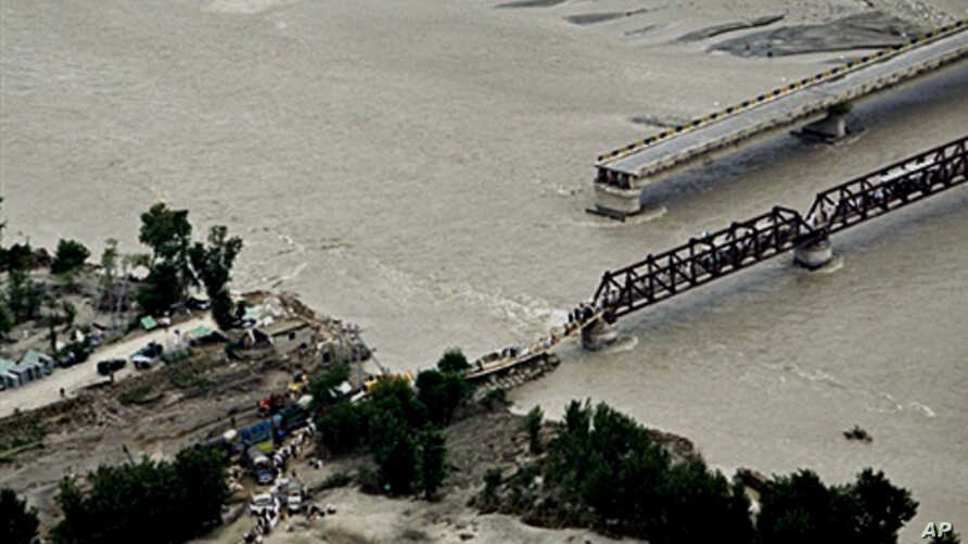 Flood survivors cross a hastily-repaired bridge next to a main bridge swept away by flood waters in Swat Valley, 10 Aug 2010