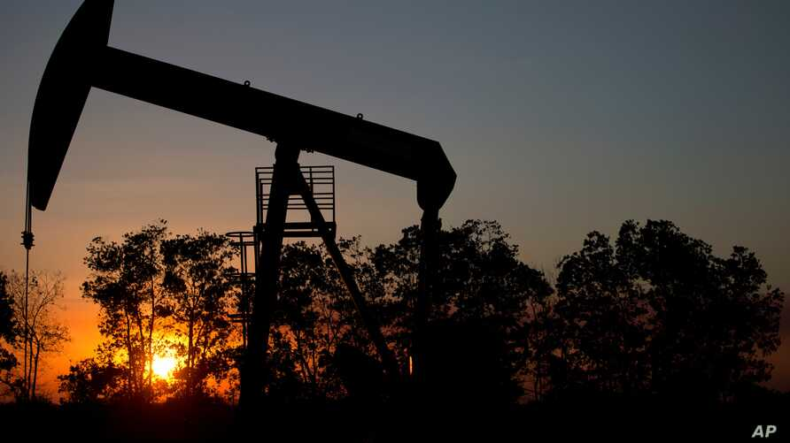 FILE - The sun sets behind an oil well in a field near El Tigre, within the Hugo Chavez oil belt in Venezuela, Feb. 19, 2015. Citgo Petroleum Corp. has bowed out of a program that has helped hundreds of thousands of U.S. residents.