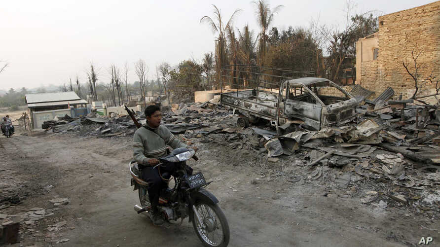 Burmese police officer rides a motorbike past debris of buildings and a truck destroyed during ethnic unrest between Buddhists and Muslims, as he provides security in Meikhtila, March 25, 2013.