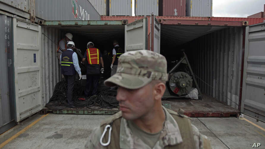 A police officer stands guard as investigation officers look inside a recently opened container holding military equipment aboard the North Korean-flagged freighter Chong Chon Gang, at the Manzanillo International container terminal on the coast of C