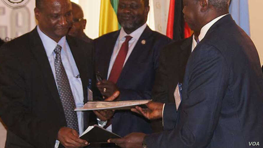Taban Deng Gai (L), lead negotiator for the South Sudanese armed opposition, exchanges a signed recommitment to stop hostilities with Nhial Deng, lead government negotiator, at an IGAD summit in Ethiopia on Nov. 9, 2014, as opposition leader Riek Mac