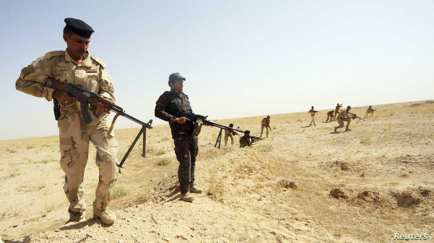 Members of Iraqi security forces take their positions during a patrol looking for militants of the Islamic State of Iraq and the Levant (ISIL) west of Kerbala, June 29, 2014.