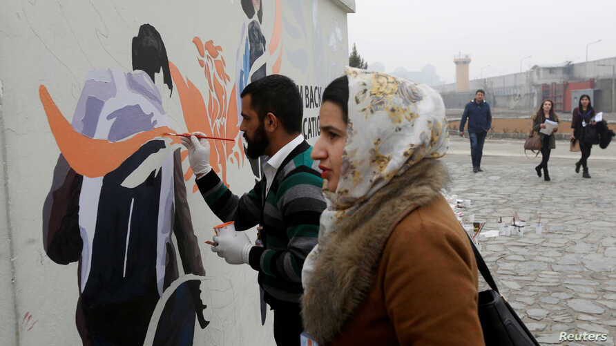 Afghan Artlords paint a message on a wall at the American University of Afghanistan in Kabul, Feb. 14, 2018.