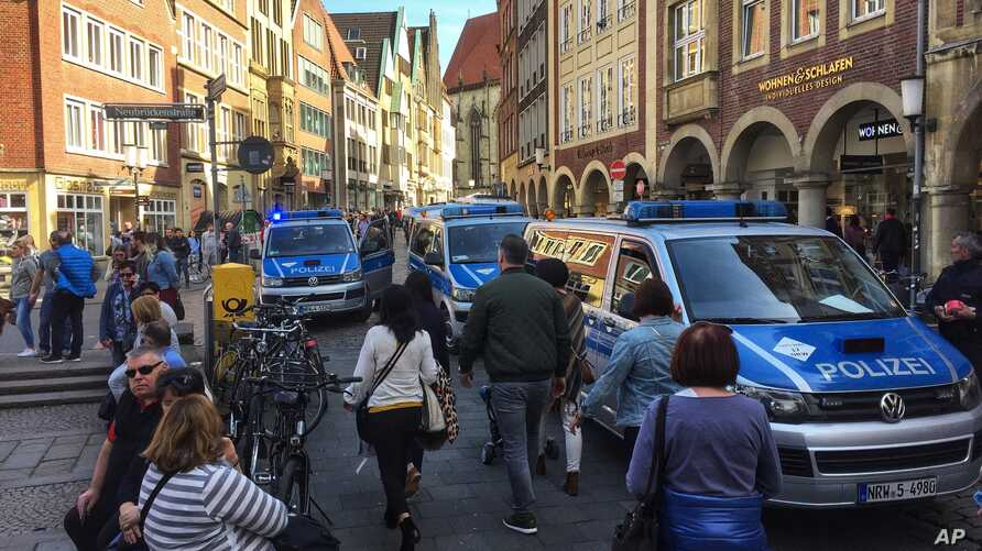 Police vans stand in downtown Muenster, Germany, April 7, 2018. German news agency dpa says several people killed after car crashes into crowd in city of Muenster.