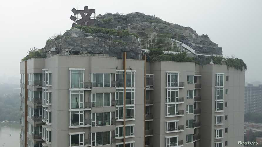 Privately built villa surrounded by imitation rocks atop a 26-story residential block, Beijing, Aug. 13, 2013.