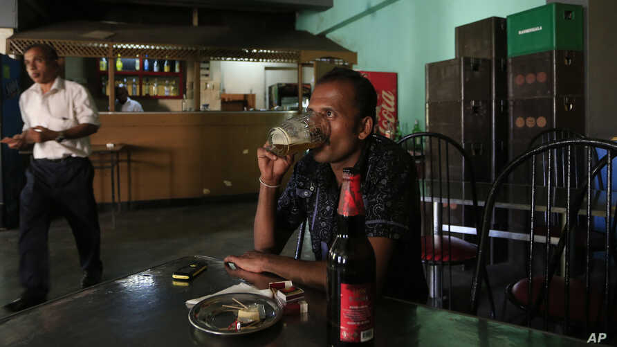 A Sri Lankan man drinks beer at a bar in Colombo, Sri Lanka, Jan. 12, 2018. The country's finance minister has reversed his earlier decision to lift a ban on selling alcohol towomen.
