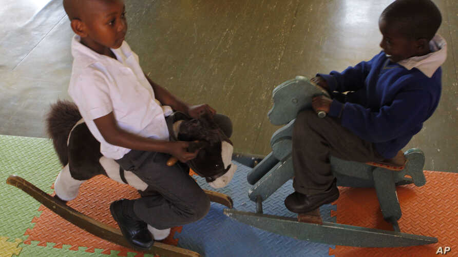 FILE - Children play on rocking horses at a toy library run by Cotlands, a local nonprofit organization that promotes early learning opportunities for children,  in Johannesburg.