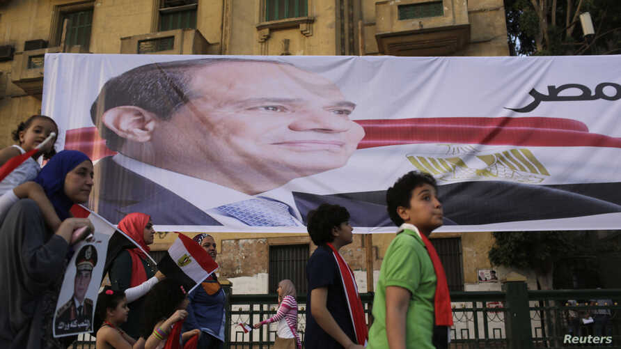 Egyptians walk by a poster for former Egyptian army chief Abdel Fattah al-Sisi in Tahrir square as they arrive to celebrate his victory in the presidential vote in Cairo, June 3, 2014.