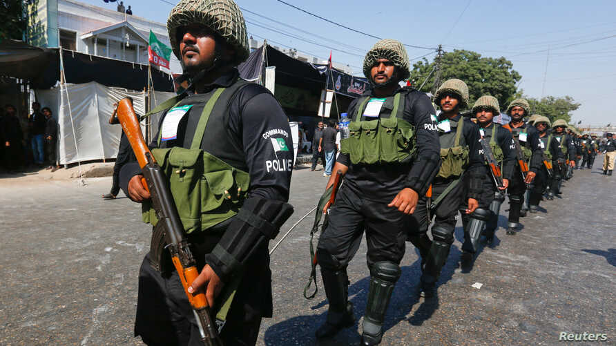FILE - Policemen walk along a road for security measures during the religious procession ahead of Ashura in Karachi, Pakistan, Oct. 11, 2016. Karachi police killed five suspected terrorists they believe were planning an attack on the day of Ashura.