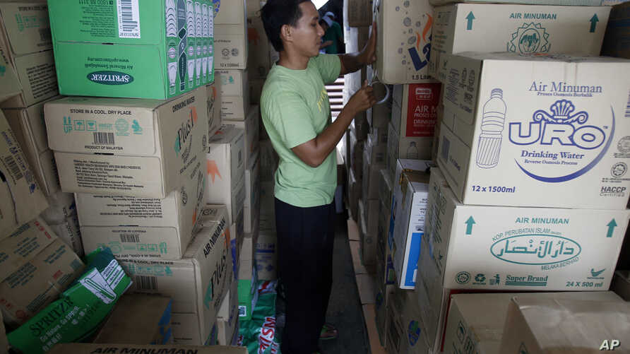A volunteer of Muslim Care Malaysia Society packs boxes of mineral water to be sent to flood-hit east coast states, in Shah Alam, outside Kuala Lumpur, Malaysia, Saturday, Dec. 27, 2014.