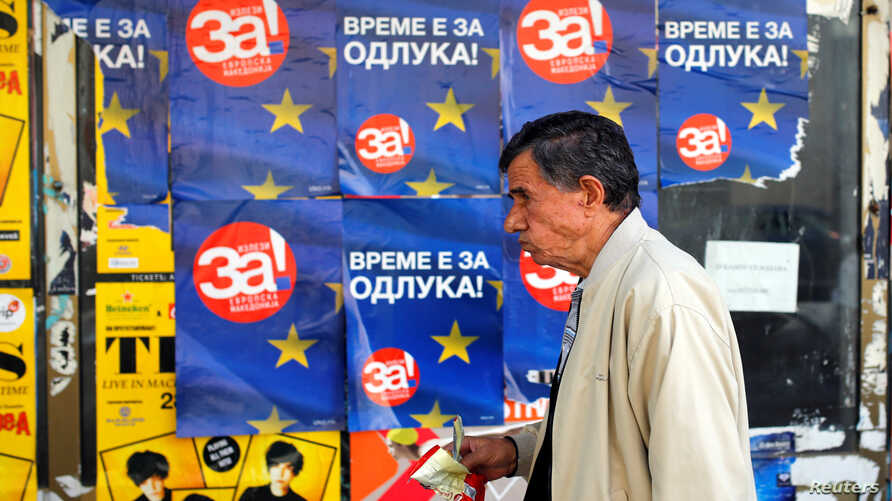 """A man passes posters reading """"yes"""" for the referendum in Macedonia on changing the country's name that would open the way for it to join NATO and the European Union, in Skopje, Macedonia, Sept. 28, 2018."""