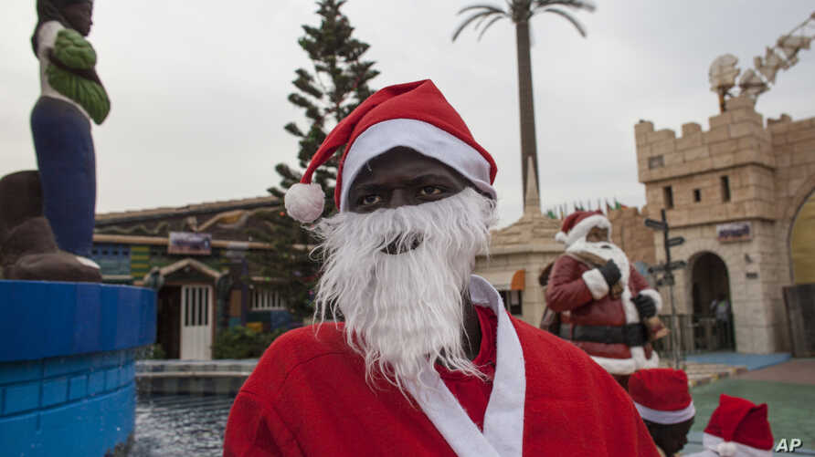 Mamadou Ngueye, who dresses as Santa Claus, waits for a guest to take a picture with at the amusement park  Darkar, Senegal, Dec. 19 2015. Ngueye, is one of many Pere Noels, or Father Christmases, seen in Senegal's capital.