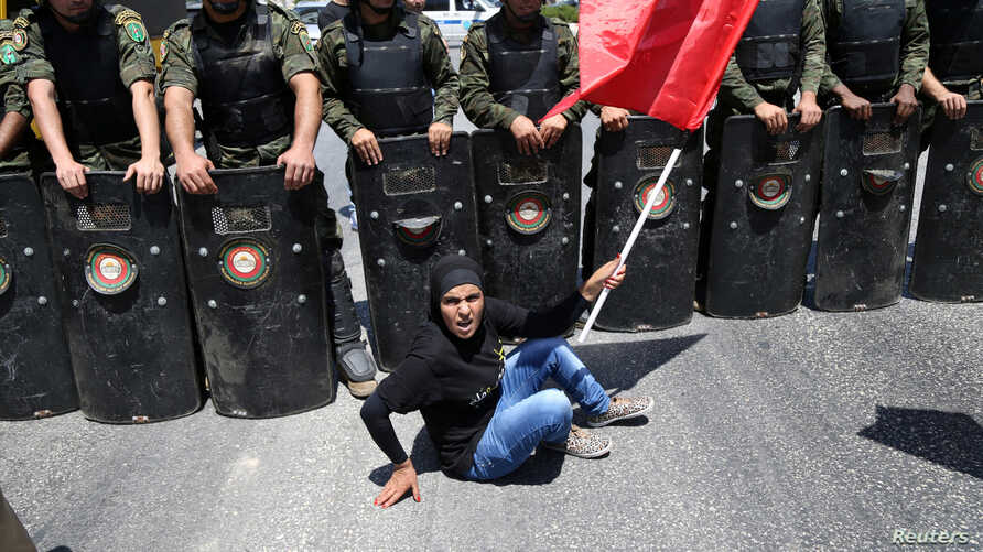 A Palestinian protester sits in front of national security force members during a protest in support of Palestinian prisoners on hunger strike in Israeli jails in the West Bank city of Ramallah August 9, 2016.