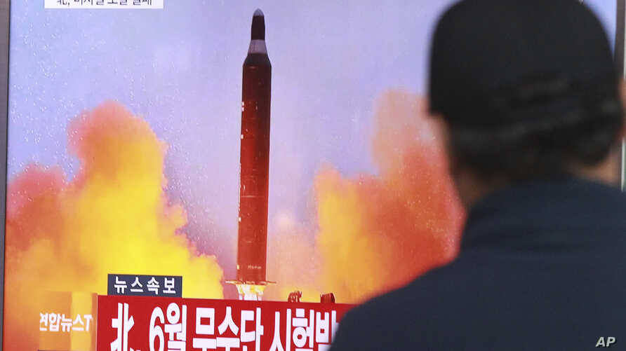 "FILE - A man watches a TV news program, Oct. 16, 2016, showing a file image of a missile launch conducted by North Korea. The letters read ""North attempted to fire a mid-range Musudan missile in June."""