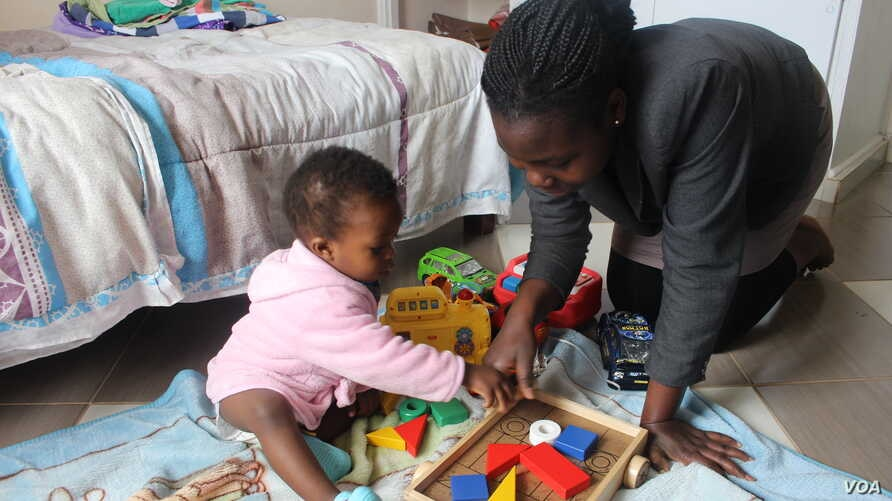 Josephine Nimile, a nanny, plays with a child at her employer's home in Nairobi, July 2015. (R. Ombuor/VOA)