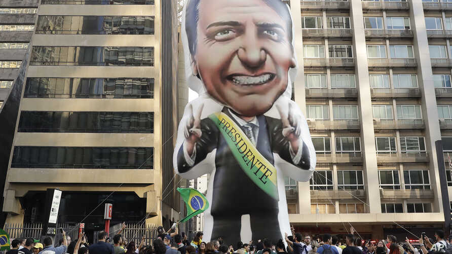 Supporters of Jair Bolsonaro, presidential candidate for the National Social Liberal Party who was stabbed during a campaign event days ago, exhibit a large, inflatable doll in his image in Sao Paulo, Brazil, Sunday, Sept. 9, 2018.