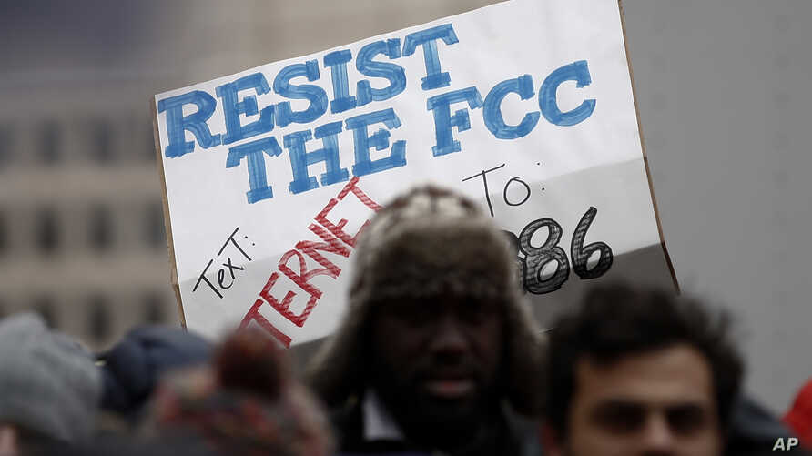 """A protester holds a sign that reads """"Resist the FCC. Text: INTERNET To: 52886"""" at the Federal Communications Commission (FCC), in Washington, Dec. 14, 2017."""
