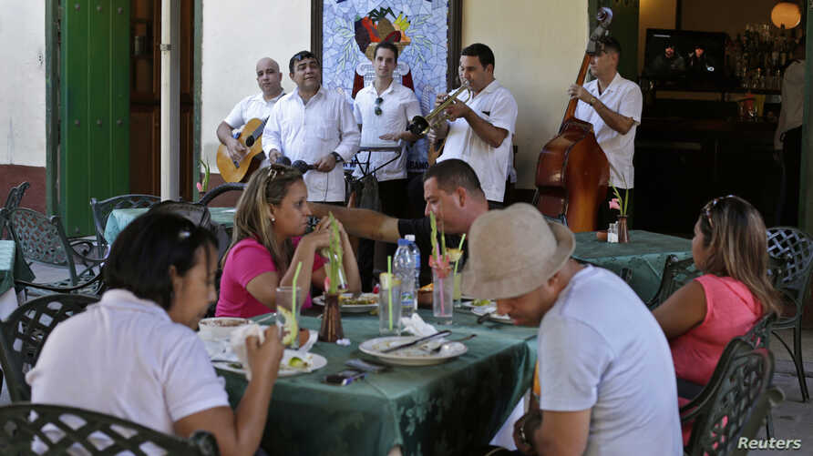 "Musicians perform as tourists dine at ""La Mina"" state restaurant in Old Havana, Cuba, Dec 18, 2014."