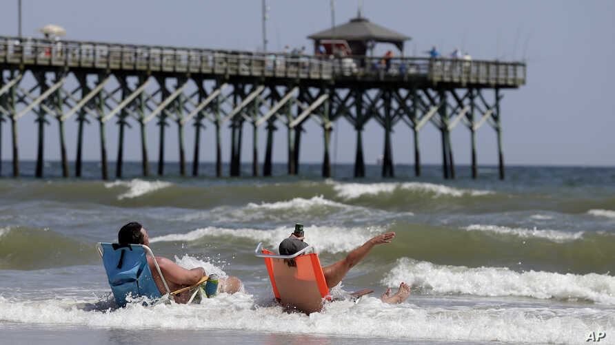 FILE - Vacationers sit in chairs along the surf in Oak Island, N.C., where two youths were hurt in shark attacks on June 14, 2015.