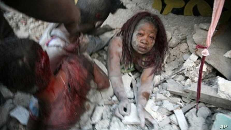 Haitian woman is covered in rubble in Port-au-Prince, 12 Jan 2010