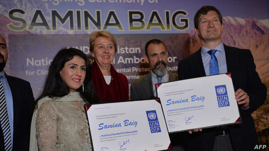 Renowned female Pakistani mountaineer Samina Baig (L) and Neil Buhne (R), the United Nations Resident Coordinator in Pakistan, display the signing documents during a ceremony in which she was appointed as Goodwill Ambassador for the United Nations De