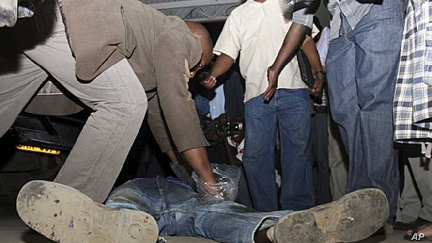 A policeman inspects pockets of a man killed in an explosion in Kenya's capital, Nairobi, March 10, 2012.