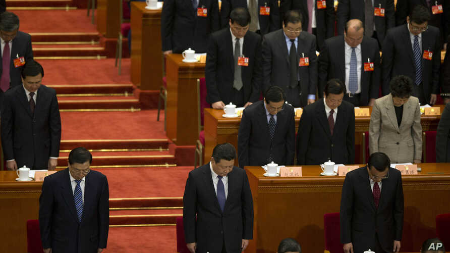 China's top leaders including Chinese President Xi Jinping, bottom center and Chinese Premier Li Keqiang, bottom right, have a moment of silence to commemorate the victims of a slashing spree during the opening session of the Chinese People's Politic