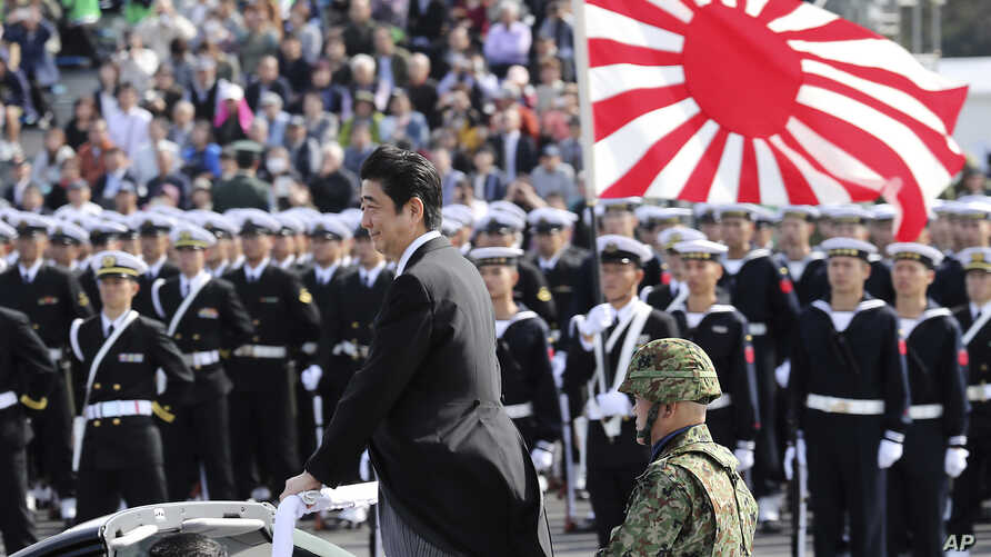 FILE - Japanese Prime Minister Shinzo Abe, center standing, reviews members of Japan Self-Defense Forces (SDF) during the Self-Defense Forces Day at Asaka Base, north of Tokyo, Oct. 23, 2016. Japan is debating whether to develop limited pre-emptive ...