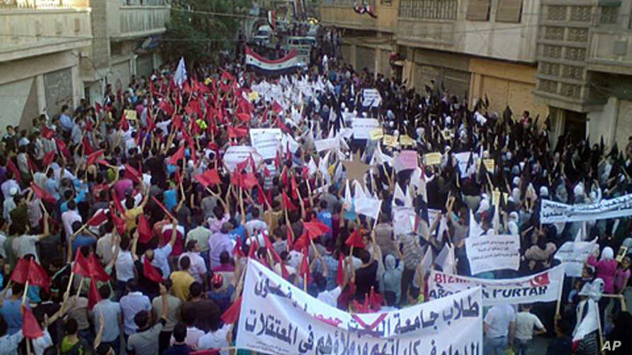 Demonstrators march through the streets in Homs.  Britain, France, Germany and Portugal Tuesday circulated a new draft U.N. resolution condemning Syria that drops previous calls for immediate sanctions against Damascus, September 27, 2011.