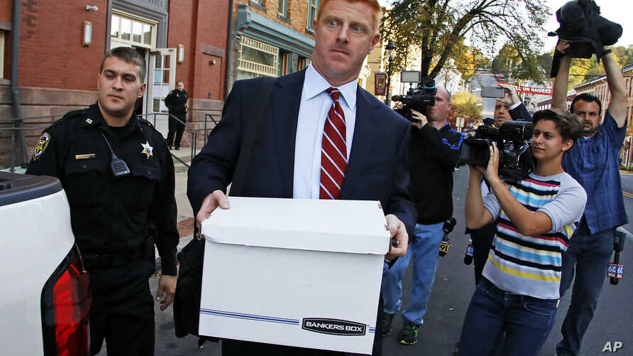 FILE -  Former Penn State University assistant football coach Mike McQueary, center, leaves the Centre County Courthouse Annex in Bellefonte, Pa., Oct. 17, 2016. McQueary was awarded $7.3 million in his defamation and whistle-blower lawsuit against P