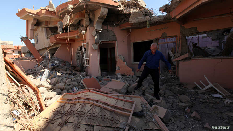 A Christian man inspects his neighbors' home, destroyed by Islamic State militants in the Christian city of Qaraqosh, Iraq, Sept. 12, 2018.