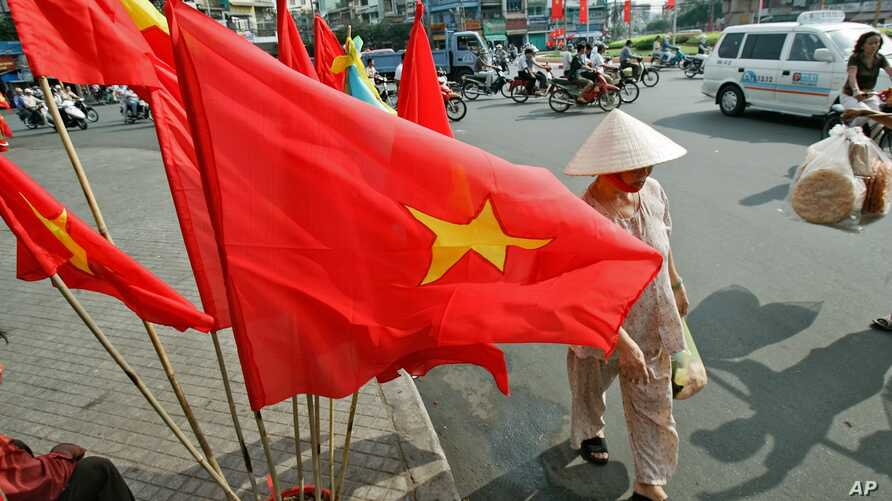FILE - Vietnamese flag sales to mark the 30th anniversary of the end of the war in Ho Chi Minh city, formerly Saigon.