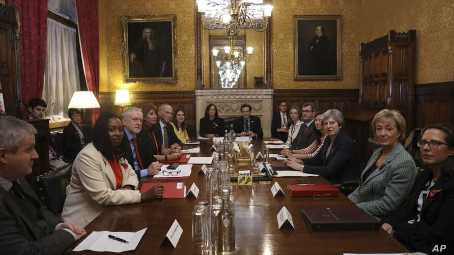 Britain's Prime Minister Theresa May, third left, sits with members of parliament during a meeting to tackle abuse following  allegations of sexual harassment and abuse in British politics, at the Prime Minister's Office in the House of Commons, Lond