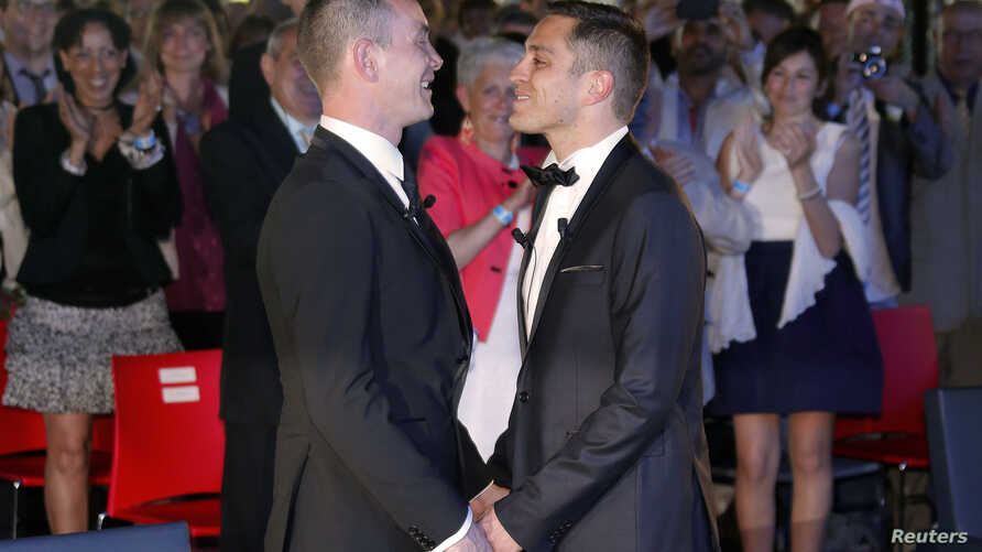 Vincent Autin (L) and Bruno Boileau hold hands after getting married at the town hall in Montpellier, France, May 29, 2013.
