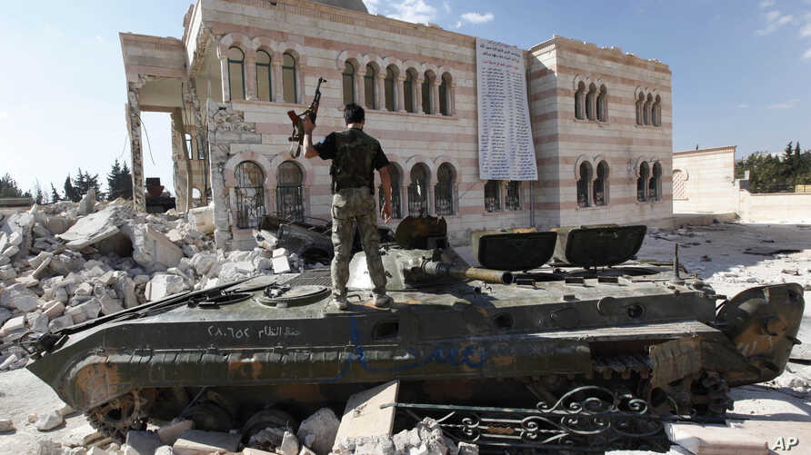 FILE - A Free Syrian Army soldier stands on a Syrian military tank in front of a mosque, which were damaged during fighting with government forces, in the Syrian town of Azaz, on the outskirts of Aleppo, Sept. 23, 2012.