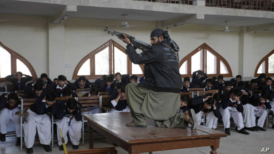 A Pakistani security official poses as a militant during a security drill Feb. 2 at the Islamia College in Peshawar, following extremists' deadly Jan. 21 attack on Bacha Khan University. Authorities have arrested the main suspect in that massacre.