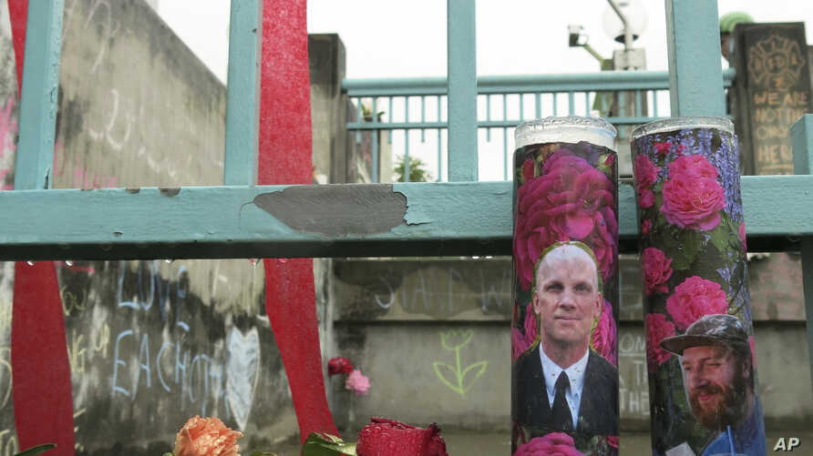 Votive candles bearing the photos of two men who were fatally stabbed on a Portland, Oregon, light-train while trying to stop another man from harassing two young women with an anti-Muslim tirade, sit on a rain-soaked memorial, May 30, 2107 in Portla